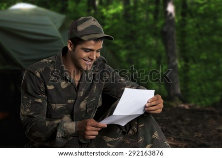 Army soldier reading a letter - stock photo