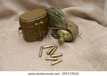 Army water bottle cap with a star, cartridges on the background fabric. - stock photo