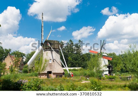 ARNHEM, NETHERLANDS - JULY 26, 2015: Classic windmills in the Netherlands Open Air museum. The museum shows the Dutch history from an everyday perspective - stock photo