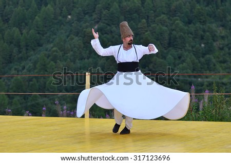 AROLLA, SWITZERLAND - AUGUST 12: Whirling Dervish from Bozdaglar in the CIME mountain culture Festival: August 12, 2015 in Arolla, Switzerland - stock photo