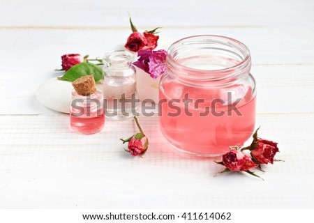 Aroma rose water for skincare, essential oils, jar and bottle, dried flowers.   - stock photo