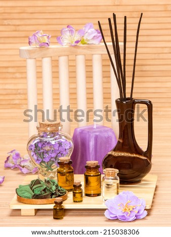 Aromatherapy accessories: floral petals, bottles filled with aromatic oils, incense sticks, candle on wooden surface