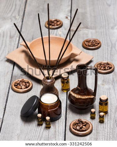 Aromatherapy and skincare accessories: open jar of cream, small glass vials of aromatic essential oils, crock, incense sticks, bamboo plate with water and coffee beans on old wooden planks - stock photo