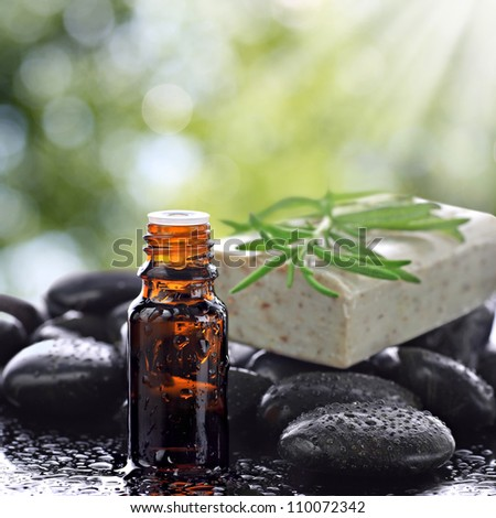Aromatherapy, essential oil bottle with natural soap bar, basalt stones and natural background - stock photo
