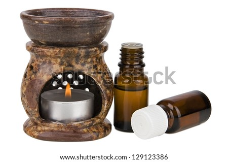Aromatherapy lamp and oils isolated on white - stock photo