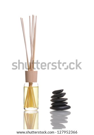 scent diffuser bottle with piled up black stones on reflective surface - Scent Diffuser