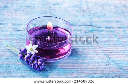 Aromatherapy spa background with a sprig of fragrant lavender alongside a burning candle with essential oil and plant extracts in a wellness and spirituality concept with copyspace - stock photo