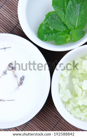 Aromatherapy treatment bowls with flowers and perfumed water on bamboo mat background - stock photo