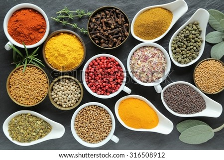 Aromatic and colorful spices in ceramic containers on a dark background. - stock photo
