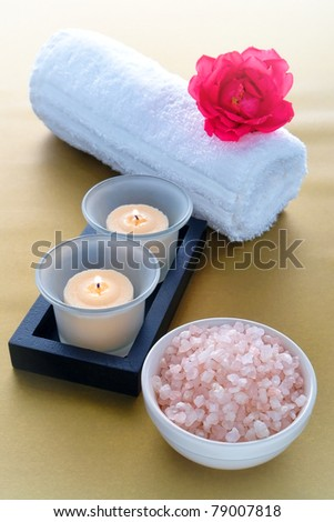 Aromatic bath salts in a ceramic bowl with burning candles in glass holders and rose flower on soft white towel over silky gold surface for pampering relaxation session in a sophisticated modern spa