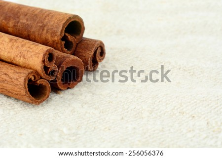 Aromatic close up set of cinnamon on white fibre material like flax - stock photo