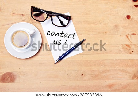 aromatic coffee on wood table with eyeglasses notepad and pen - contact us - stock photo