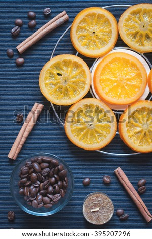 Aromatic composition of caramelized oranges, cinnamon, aromatic candle and coffee beans on a dark blue background. Top view. Low contrast toned - stock photo