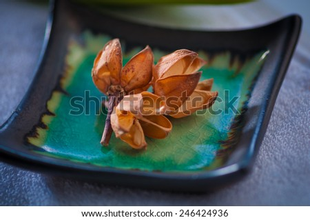 Aromatic dry flowers in an asian tray - spa elements - stock photo