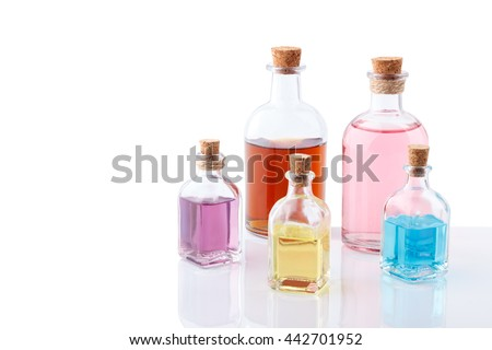 Aromatic essential oils in vintage bottles,different colors, isolated on white with reflection - stock photo