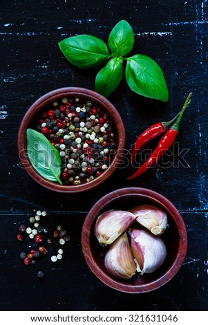 Aromatic fresh herbs and spices (pepper, garlic and basil leaves) on dark vintage background with space for text. Vegetarian food, health or cooking concept. - stock photo