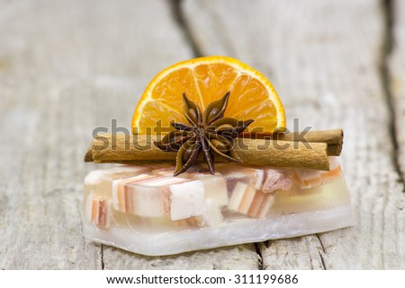 aromatic glycerin soap, orange and spices on wooden background - stock photo