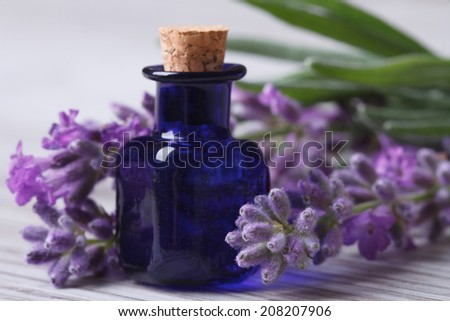 aromatic lavender oil in the blue bottle and flowers on wooden table. Horizontal close-up   - stock photo