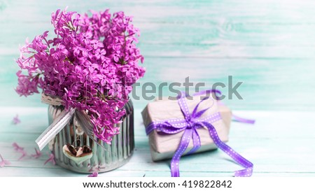 Aromatic  lilac flowers in vase and boxes with gifts on turquoise background. Selective focus. Place for text. Toned image. - stock photo