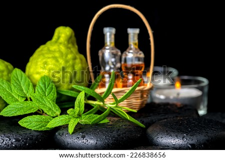 Aromatic spa of bottles essential oil in basket, fresh mint, rosemary,  bergamot fruits and candles on black zen basalt stones  - stock photo