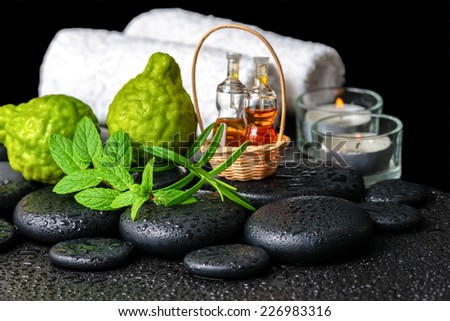 Aromatic spa still life of bottles essential oil, fresh mint, rosemary, bergamot fruits, towels and candles on zen stones  - stock photo