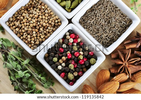 Aromatic spices in white bowls on wooden background with nuts and herbs - stock photo