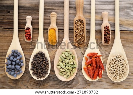 Aromatic spices on wooden spoons. Food ingradients. - stock photo
