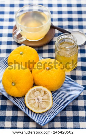 Aromatic zest of ripe fruits of yuzu combined with honey makes a syrup used to make yuzu tea (Yuzu cha, or Yujacha), a traditional Korean hot drink (herbal tea) popular in Japan. - stock photo