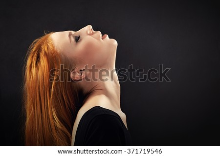 aroused woman with red hair on black background with copyspace