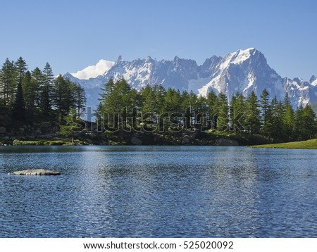 Arpy lake wonderful place in italian mountains surrounded by trees. Mont Blanc massif in background reflecting in the water