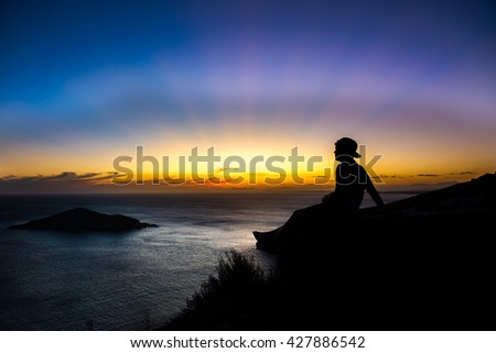 Arraial do Cabo, Brazil apr 24, 2016: Boy enjoying the sunset at the  crystalline and turquoise beaches of Pontal do Atalaia, Arraial do Cabo, Rio de Janeiro, Brazil.