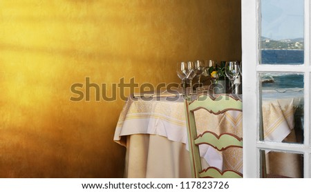 Arranged table in a restaurant and open window. Reflection of the sea on the window .Copy spice on the wall - stock photo