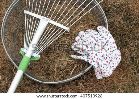 Arrangement of basket with dry grass, a radial rake and gloves on the background of dry grass. - stock photo