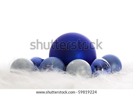 Arrangement of blue Christmas baubles on white fur - stock photo