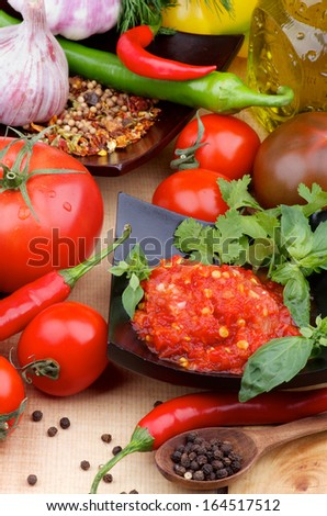 Arrangement of Bruschetta Sauce in Black Bowl with Tomatoes, Greens, Spices, Garlic and Black Peppercorn in Wooden Spoon closeup on Wooden background - stock photo
