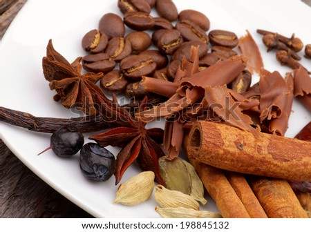 Arrangement of Coffee Beans and Cinnamon Stick with Chocolate Slices, Vanilla Pods, Anise Stars, Cardamon and Barberry on White Plate closeup - stock photo