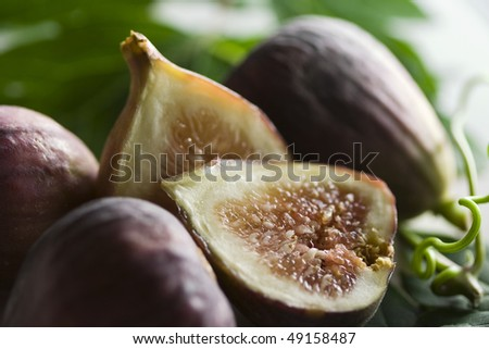Arrangement of figs on green leaves with blurry background - stock photo