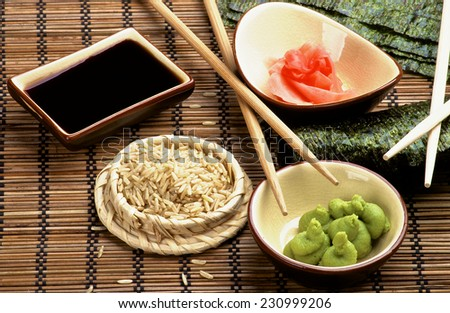 Arrangement of Ingredients to Preparing Sushi  with Nori, Ginger, Wasabi, Rice, Soy Sauce and Two Chopsticks on Bamboo Straw Mat - stock photo