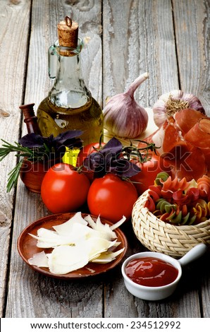 Arrangement of Raw Rotini Pasta with Tomatoes, Spices, Smoked Ham, Olive Oil and Grated Cheese isolated on Rustic Wooden background