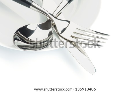 Arrangement of Silverware with Table Knife, Spoon and on White Plate isolated on white background - stock photo