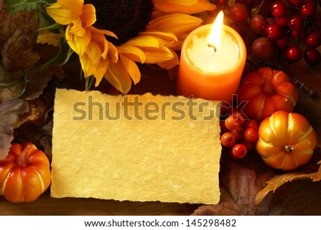Arrangement of sunflower, candle and autumn decorations on wooden background with paper copy space. - stock photo