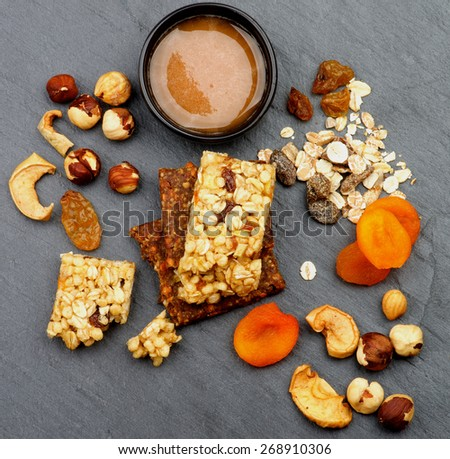Arrangement of Useful Granola Bars with Muesli, Nuts, Seed, Raisins, Dried Apricots and Bowl of Honey closeup on Black Stone background - stock photo