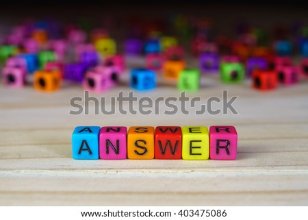 Arrangement of word ANSWER with colorful beads on wooden table. - stock photo