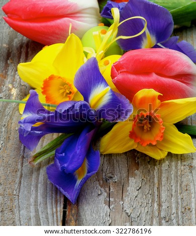 Arrangement of Yellow Daffodils, Magenta Tulips, Purple Irises with Yellow and Green Spotted Easter Eggs closeup on Rustic Wooden background