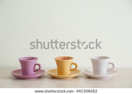 Arrangement pile of colorful modern coffee cups on wooden table with the dishes for prepare serve.
