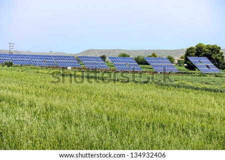Array of photo-voltaic panels in green field - stock photo