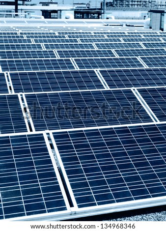Array of solar panels in rows on a roof of a building in a city - stock photo