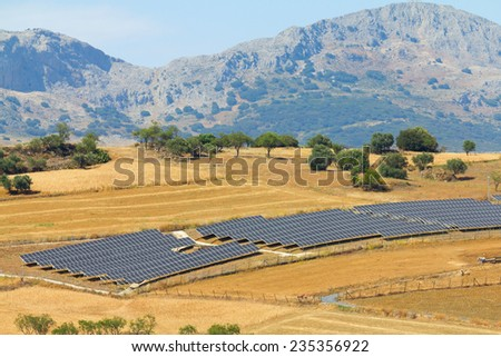 Array of solar panels in sunny rural area - stock photo