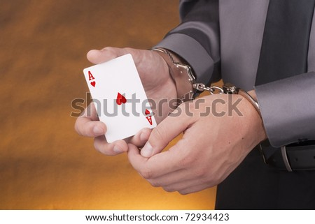 Arrest card sharper, her hands handcuffed in one of the hands of an ace. - stock photo