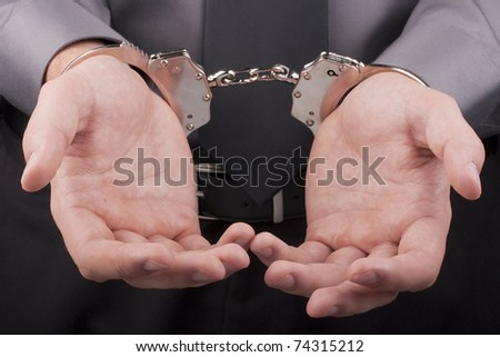 Arrest, close-up shot man's hands with handcuffs. - stock photo